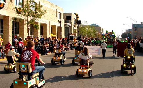 Volunteers ride carts and carry a banner in MU parade.
